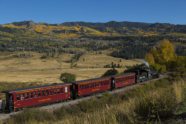 Picture of the Cumbres and Toltec Railroad making way through a mountain meadow to the train station in Chama, New Mexico